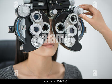 young girl patient on reception at doctor ophthalmologist. diagnostic ophthalmologic equipment. optical machine. medicine concept - Stock Image