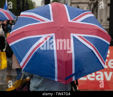 London, UK. 18th June 2019.  Tourists and Londoners protecting themselves against the continuous rain in central London today. The Union Jack umbrella appears to be very popular. Credit: JoeKuis / Alamy - Stock Image