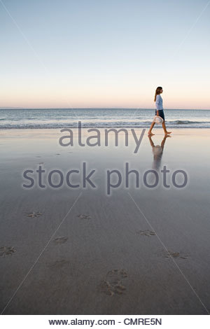 Woman walking by the sea - Stock Image