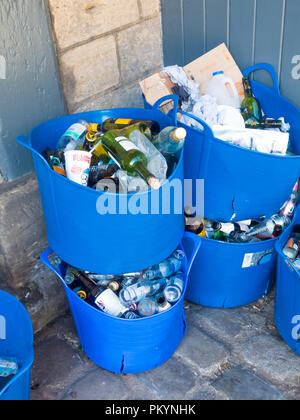 Recycling blue containers for beer and wine bottles and outside a public house - Stock Image