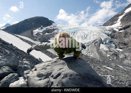 Eight year old blond girl performing acrobatic gymnastics in front of  Storbreen glacier at Jotunheimen in Norway - Stock Image