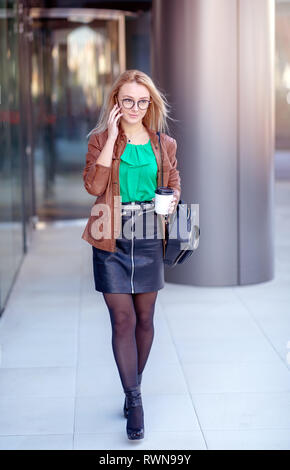 Cheerful Attractive Blonde Girl speaking on the phone exiting a modern building. Job Interview. Wearing Stylish Fashion Optical Eye Glasses - Stock Image
