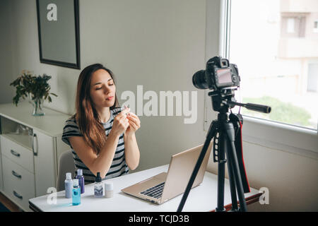 Girl videoblogger or beauty blogger records video for subscribers. She shows lipstick and tells how to use it properly. - Stock Image