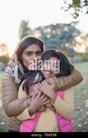 Portrait happy Muslim mother in hijab hugging daughter in park - Stock Image