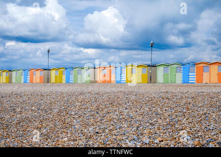 A line of 22 colourful beach huts running through the centre of the image, below is a yellow pebble beach and above is a dramatic blue and white cloud - Stock Image