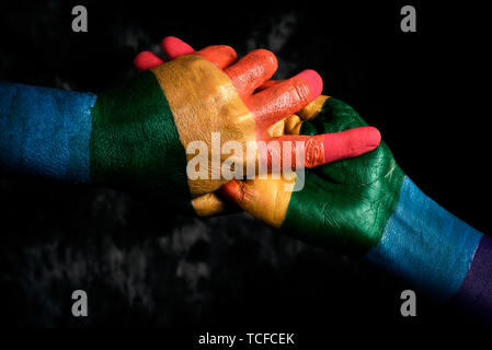 closeup of two men holding hands, painted as the rainbow flag, against a dark gray background - Stock Image