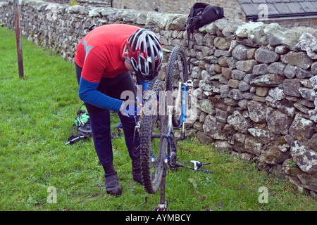 Cyclist repairing a broken chain during Mountain Bike trip in Yorkshire Dales, Great Britain - Stock Image