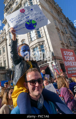 London, UK. 20th October 2018. A child with a painted face and poster on her father's shoulders on the People's Vote March calling for a vote to give the final say on the Brexit deal or failure to get a deal as the march leaves Hyde Park Corner. They say the new evidence which has come out since the referendum makes it essential to get a new mandate from the people to leave the EU. Peter Marshall/Alamy Live News - Stock Image
