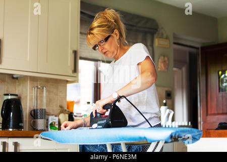 Woman ironing clothes, domestic chores, ironing clothes, woman using iron, ironing, pressing clothes, using ironing board, woman using iron, housework - Stock Image