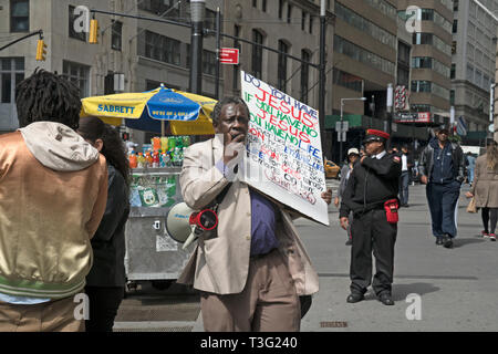 Among tourists and office workers, a man walked down Broadway in Lower Manhattan with a bullhorn and a sign about Jesus. - Stock Image