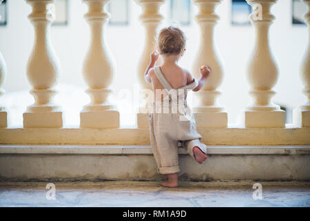 A rear view of small toddler girl looking through concrete railing on summer holiday. - Stock Image