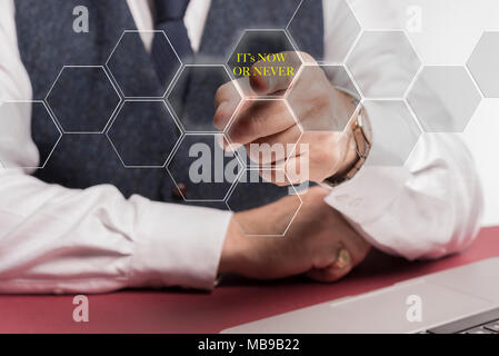"""A smartly dressed business man sitting at a desk whilst pushing a virtual button on the screen saying """" it's now or never """" - Stock Image"""