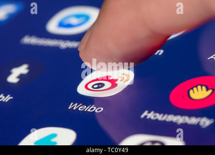Finger pressing the Sina Weibo shortcut icon for the Chinese microblogging app on the touchscreen of a mobile device. - Stock Image