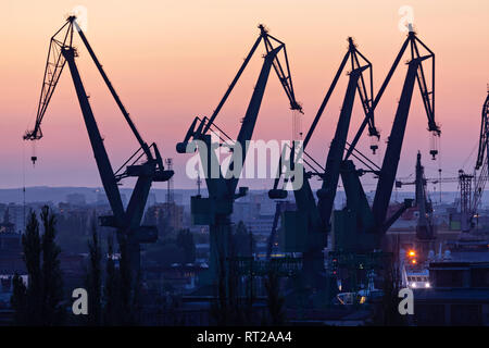 Gdansk, Poland. Silhouettes of port cranes at sunset - Stock Image