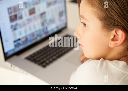 Young girl searching internet on laptop - Stock Image