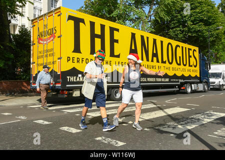Abbey Road, London, UK.  29th June 2019.  UK Weather:  Tourists crossing the famous Abbey Road zebra crossing made famous by The Beatles in an elf and a santa hat on a scorching hot day in London.  A lorry is parked on the road which has advertising on it for 'The Analogues' Beatles musical.  Picture Credit: Graham Hunt Photography. Credit: Graham Hunt/Alamy Live News - Stock Image