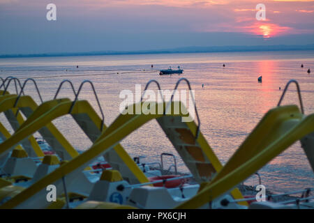 Pedalos at the lake during sunset - Stock Image