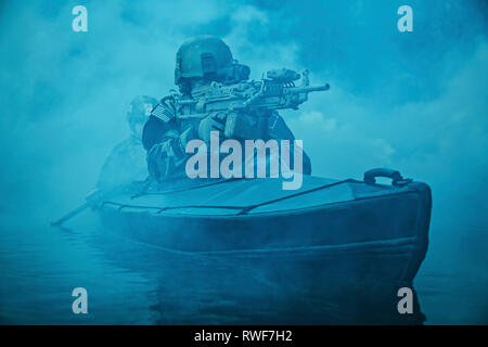 Special forces operator armed with machine gun, paddling Army kayak through river fog. - Stock Image