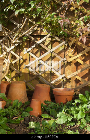 Old clay terracotta flowerpots by the fence at the bottom of the garden. - Stock Image