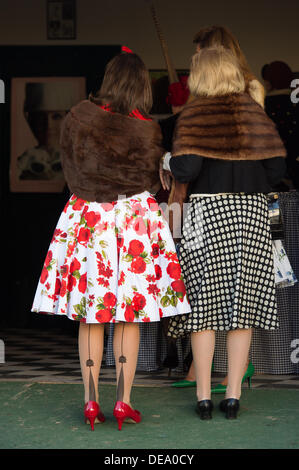 Chichester, West Sussex, UK. 14th Sep, 2013. Goodwood Revival. Goodwood Racing Circuit, West Sussex - Saturday 14th September. Two ladies look into the beauty salon wearing vintage clothing including patterned seamed stockings and a floral red rose dress with fur wraps. Credit:  MeonStock/Alamy Live News - Stock Image