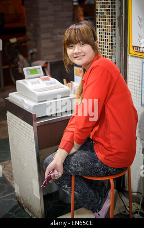 Young cheerful Chinese woman working as a cashier at a cash register in a family restaurant. China; Young lady; - Stock Image