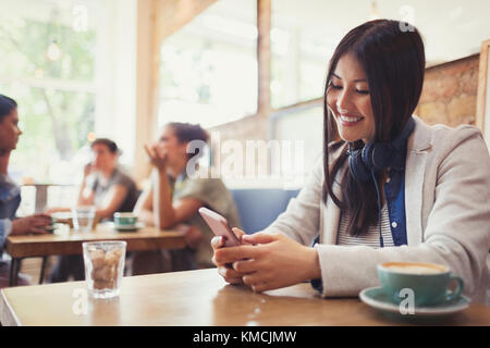Smiling young woman with headphones texting with cell phone and drinking coffee at cafe table - Stock Image
