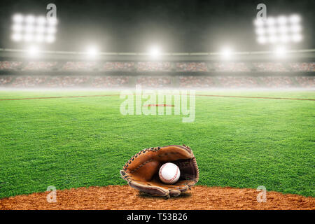 Baseball glove on field at brightly lit outdoor stadium. Focus on foreground and shallow depth of field on background and copy space. - Stock Image
