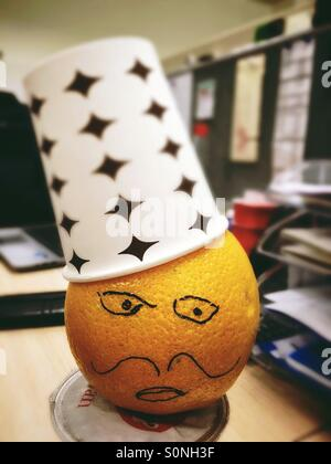 Office fun with an orange man wearing hat made by paper cup. - Stock Image