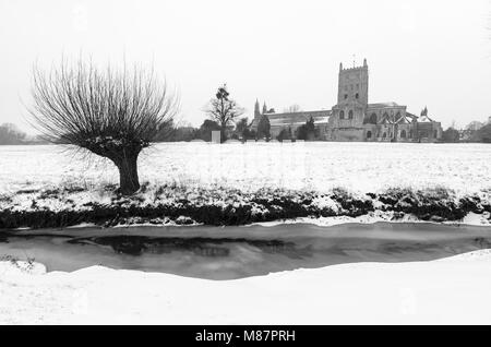 Tewkesbury Abbey and the frozen River Swilgate in the Snow - Stock Image