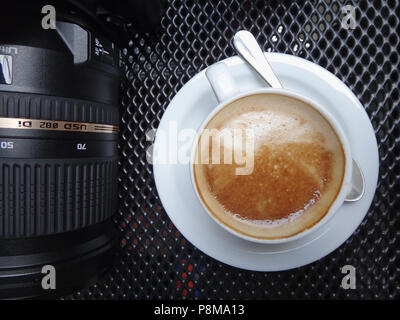 Horizontal close-up shot of cropped camera and camera lens and a latte in a white cup with saucer and spoon - Stock Image