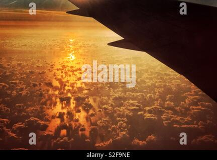 The view from an aircraft window looking at the sunrise over the Bay of Biscay. Yellow light is reflected off the Atlantic Ocean &helps outline the interesting cloud formations. Photo © COLIN HOSKINS. - Stock Image