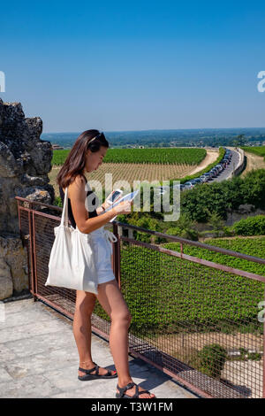 A young woman looks out from the Tour du Roi (King's Tower) in St Emillion in the Bordeaux region of France. - Stock Image