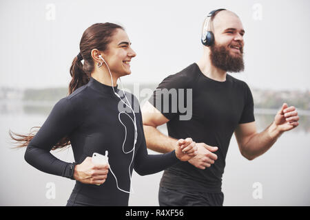 Couple jogging and running outdoors in park near the water. Young bearded man and woman exercising together in morning - Stock Image