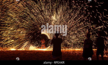 Sparks fly spiralling in an impressive display at a beach fire show, thailand. - Stock Image