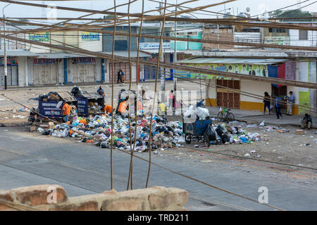 Chaotic street scene: crossed cables and garbage collection outside one of the markets of Piura in Peru. - Stock Image