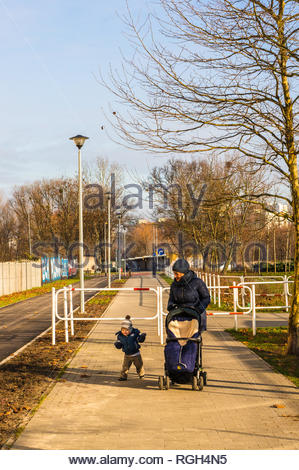 Poznan, Poland - January 19, 2019: Woman with buggy and toddler boy walking on a footpath in the Rataje park. - Stock Image