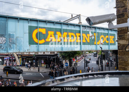 Security CCTV camera in foreground overlooking Camden Marketplace and iconic painted Camden Lock sign on side of railway bridge  in London with street - Stock Image