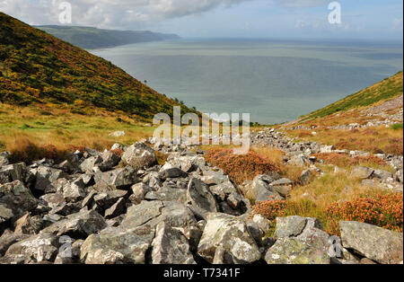 The rock strewn valley down which the South West coast path descends from Bossington Hill to Porlock Weir with a view across Porlock bay to the distan - Stock Image