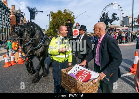 London, UK. 13th October 2018. A police officer tries to stop the funeral procession of cyclists behind a horse-drawn hearse to highlight the failure of governments from all the major parties to take comprehensive action on safer cycling. Stop Killing Cyclists call for £3 billion a year to be invested in a national protected cycling network and for urgent action to reduce the toxic air pollution from diesel and petrol vehicles which kills tens of thousands of people every year, and disables hundreds of thousands. The several hundred protesters staged a ten-minute die-in outside Parliament befo - Stock Image