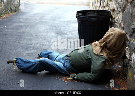 Halloween scarecrow left out with the trash in a driveway - Stock Image