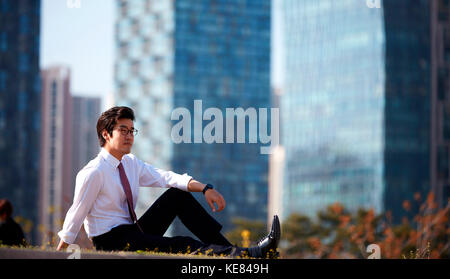 Side view of businessman resting at park during daytime - Stock Image