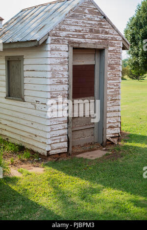 An old weathered wooden tool shed with peeling paint and a tin roof on a rural farm in Oklahoma, USA. - Stock Image