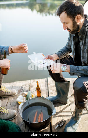 Two fishermen sitting together with fishing tackles sitting during the picnic near the lake - Stock Image