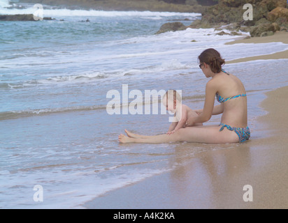Young mother and child relaxing in the surf on a Puerto Rican beach. - Stock Image