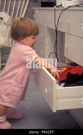 toddler pulling things out of drawer in danger of accident with hair dryer - Stock Image