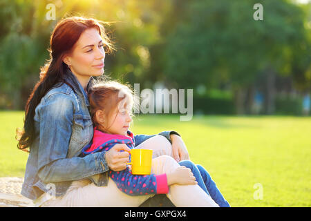 Beautiful calm female with her little precious daughter drinking morning tea outdoors, peaceful weekend in the camping - Stock Image