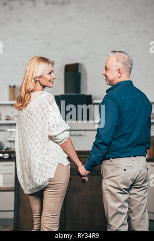 happy couple standing and smiling while holding hands - Stock Image