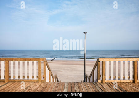 Wooden boardwalk with a beach entrance. - Stock Image