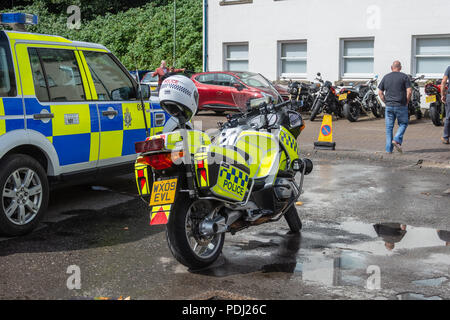 A police BMW motorcyle with a police crash helmet on the rear blue lamp next to a police 4x4 on display at the 2018 Calne Bike meet - Stock Image