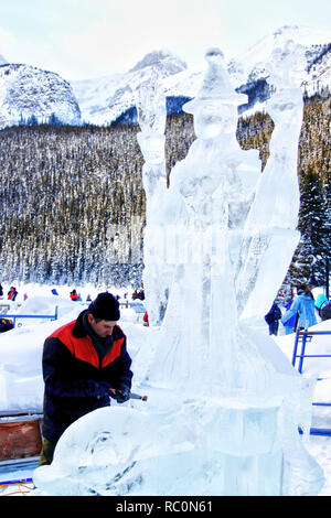 LAKE LOUISE, CANADA - JAN 22, 2011: An ice sculptor carves a tall block of ice with a power tool during the annual Ice Magic Festival held in the Cana - Stock Image